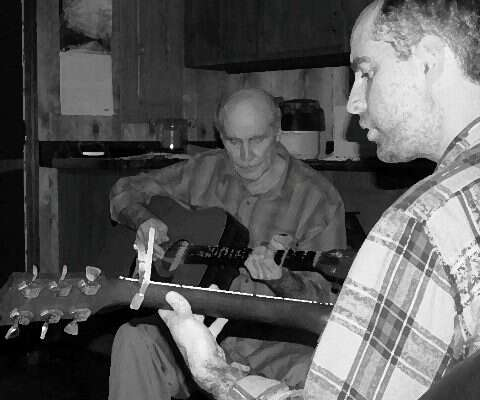 two men playing guitars