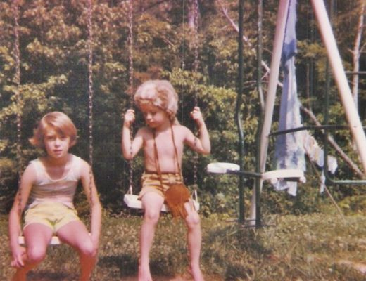 Boy in coonskin cap and girl on swingset