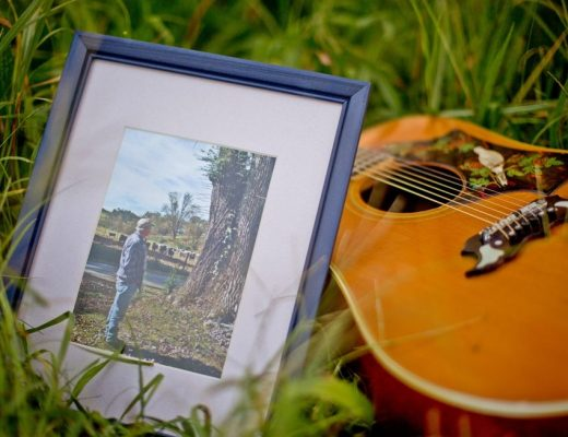 picture of man laying against guitar in the grass