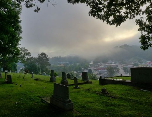 grave yard with mountains covered in fog in background