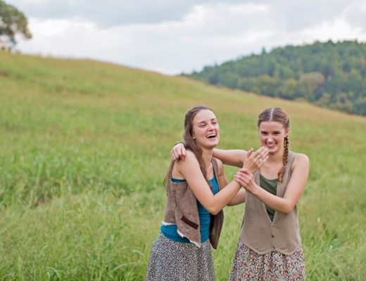 two girls laughing in a field of grass