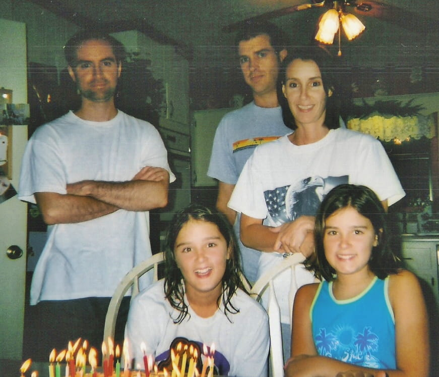 family sitting at table with birthday cake