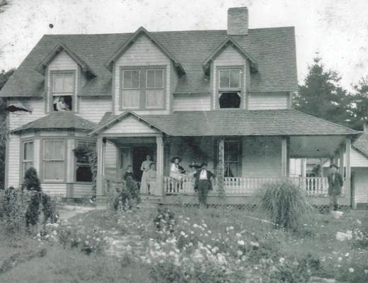 Picture of old house with people standing on porch